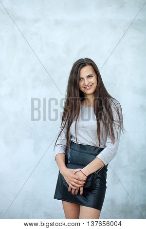 Young Beautiful Brunette Woman In Black Leather Skirt With Clutch Standing Near Wall, Outdoors Fashi