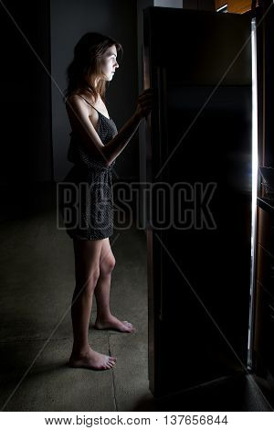 Woman craving and looking for food in an empty frige late at night