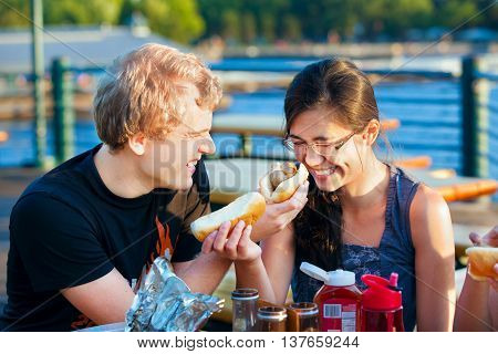 Young couple eating hotdogs by the lake having fun