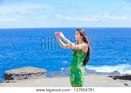 Beautiful biracial Thai Caucasian teen girl standing on tropical Hawaiian beachi holding camera taking pictures or videos