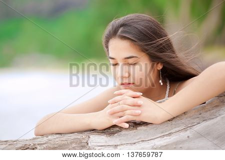 Beautiful biracial asian Caucasian teen girl on secluded beach praying by driftwood log in sunny Hawaiian setting