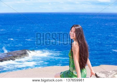 Beautiful biracial teen Asian Caucasian girl sitting on rocky ledge overlooking blue ocean off the coast of Hawaii on sunny day