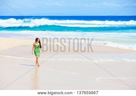 Beautiful biracial Asian Caucasian teen girl in green dress walking along empty secluded Hawaiian beach waves crashing onto shore on sunny day