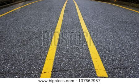 yellow line on street divided between car at parking lot of loading area