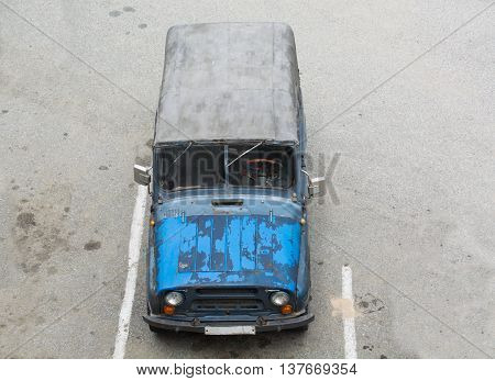 Old russian car with shabby blue paint stay on parking. A canvas top.