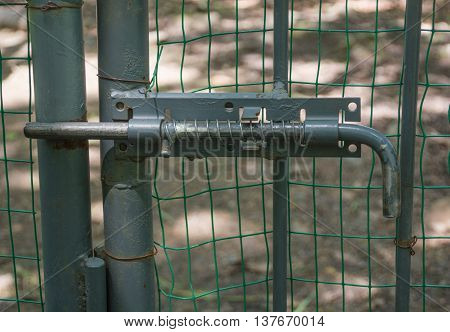 Old rusty metal fence closed with latch lock