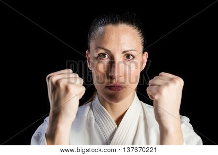 Portrait of female fighter performing karate stance on black background