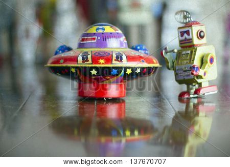tin ufo and small robot on wooden floor