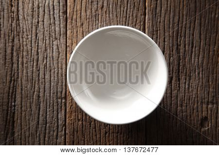 top view of ceramic bowl on the wooden background