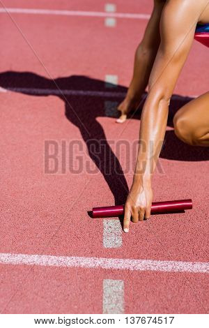 Mid-section of female athlete ready to start the relay race on the running track
