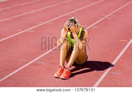 Upset female athlete sitting on running track on a sunny day