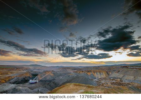 Coal mining in open pit at the sunset.