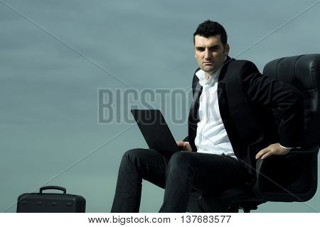 handsome male businessman with courageous face in black formal jacket and white shirt working on laptop sitting on leather office arm chair with briefcase outdoor on cloudy sky background