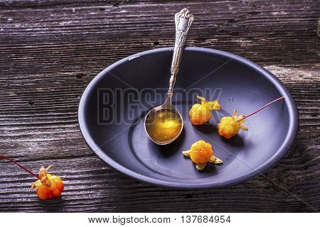 Black simple dish with a spoon Arctic cloudberry seed oil full with ripe fresh berries north cloudberries in plain wooden background in rustic background.