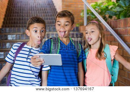 School kids taking selfie from mobile phone at school