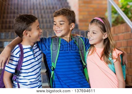 Smiling school kids standing with arm around at school