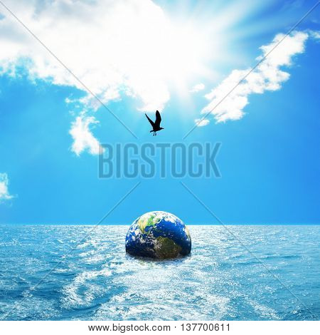 conceptual image of globes floating in sea over sunny sky. NASA globe image used