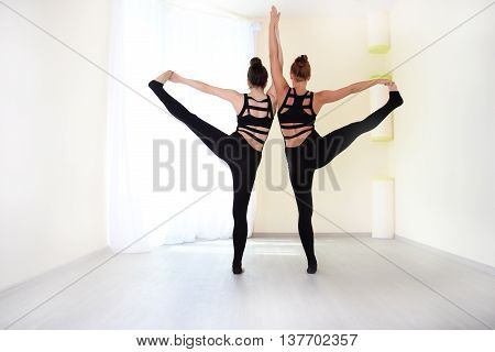 Athletes dressed in a stylish tracksuit standing on one leg and holding hands view from the back. Practicing yoga exercises