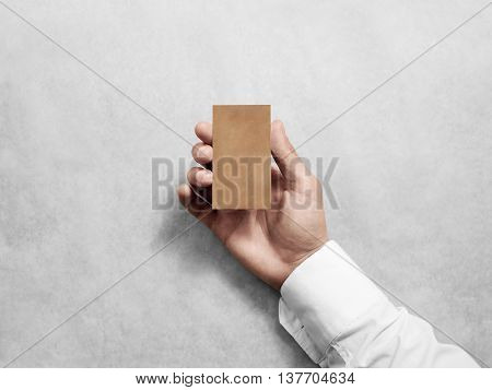 Hand hold blank vertical craft business card design mockup. Brown calling card mock up template holding arm. Visit pasteboard kraft paper display front. Small offset texture card print. Logo branding