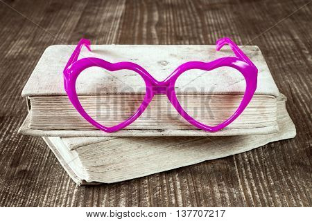 Love to read concept with books and heart shaped glasses