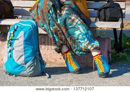 Legs of Tourist resting on wooden bench in park with backpack and camera bag dressed in Casual bright Pants Bloomers style and blue Sport Shoes