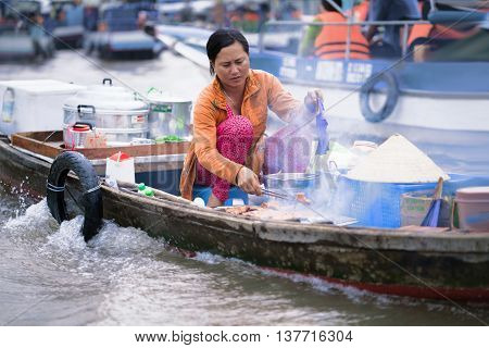 Woman Cooking In The Floating Market In Can Tho