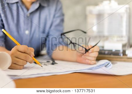 business architect drawing  blueprint on woodden table architectural concept soft focus