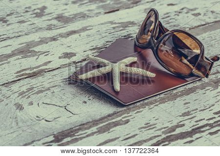 Travel, holiday and vacation in the summer tranquility and relaxation concept with passports starfish and sunglasses on a grunge wooden table. Selective focus macro close up.