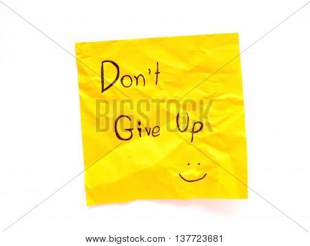 Write don't give up on yellow post note isolated on white background