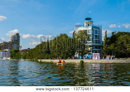 YEKATERINBURG RUSSIA -AUGUST 24 2013. Summer architecture urban view- residential modern architecture and sports complex Dynamo building with people on the embankment