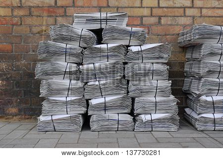 stacked and bundled tabloid newspapers on sidewalk