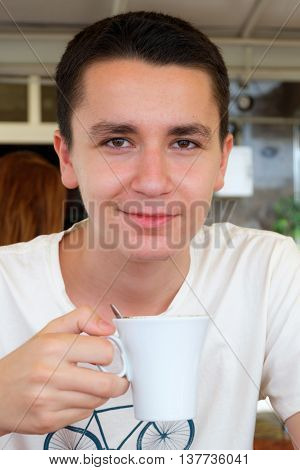Portrait of young handsome man drinking coffee and smiling in cafe
