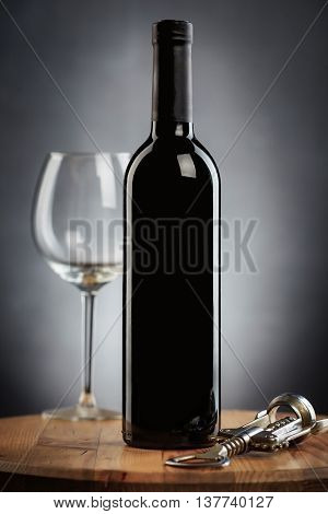 Bottle Of Wine With A Glass And A Corkscrew On A Wooden Table On Gray Background
