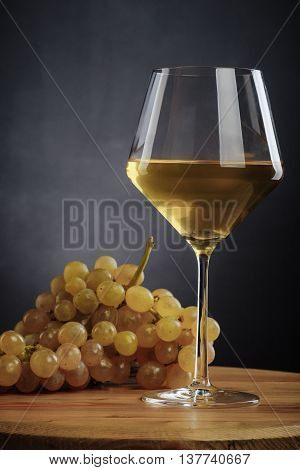 glass of white wine and grapes on a wooden table