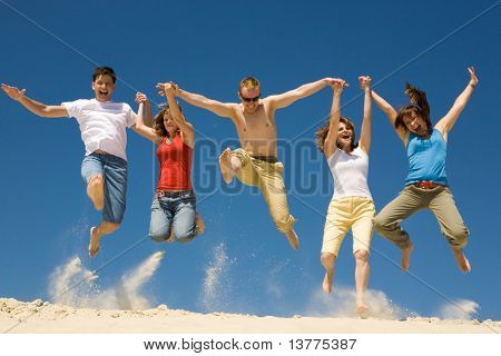 Photo of excited people jumping on sandy beach with their arms raised against blue sky