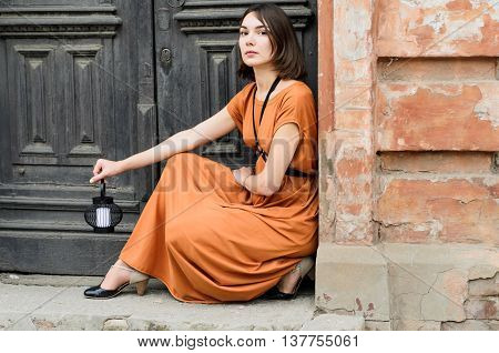 Beautiful boho style girl in a long dress posing in the street