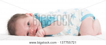 Newborn baby boy with open keen eyes laying in his bed with white background
