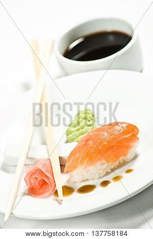 Нигири-суши с палочками на тарелке имбирь васаби соевыйсоус