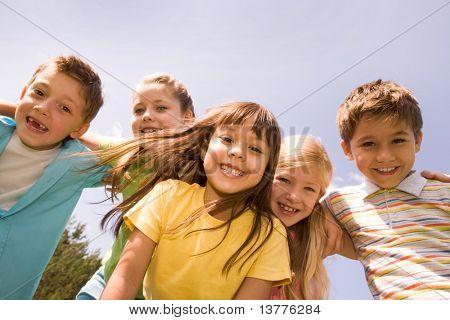 Porträt der glückliche Kinder umarmen einander und mit hübschen Mädchen vor Lachen