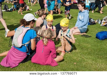 Tauranga, New Zealand - April 1, 2012; Children on ground ready for swimming leg of event with swimming tog and caps with numbers waiting