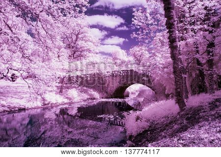 Stunning Infrared Landscape Image Of Old Bridge Over River In Countryside