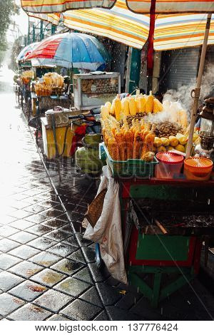 Street food stall with grilled corn under the rain Ubud Bali Indonesia