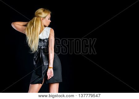 a young woman with loose long fair hair in a nice short dress standing in the black background for advertising