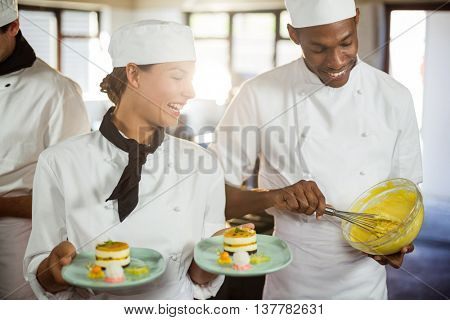 Female chef presenting dessert plates in commercial kitchen