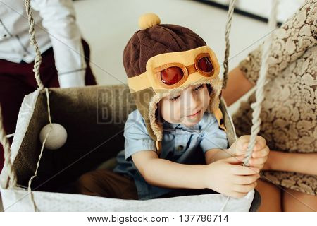 Happy boy having fun in handmade basket of air balloon. Child play at home with parents. Young pilot indoors. Boy in hat like a helmet and bowtie looking away.