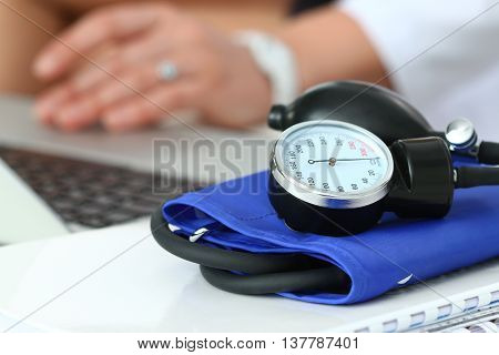 Close up view of manometer laying on working table. Hospital workspace. Healthcare medical service treatment hypotonia or hypertension concept. Female doctor work at laptop on background. Copyspace