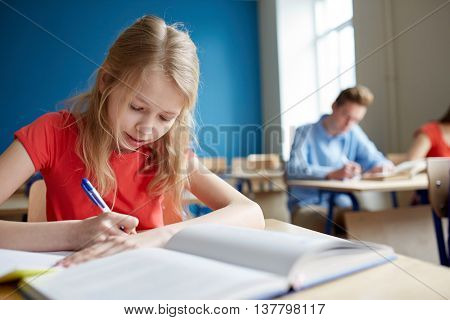 education, learning and people concept - student girl with book writing school test