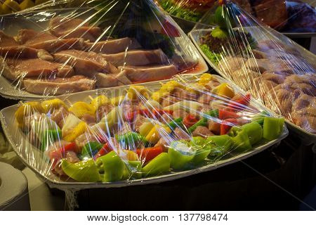 Raw meat in plastic wraps prepared for a BBQ buffet at the wedding.