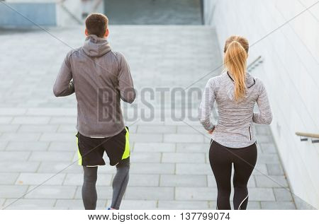 fitness, sport, people, exercising and lifestyle concept - couple running downstairs on city stairs