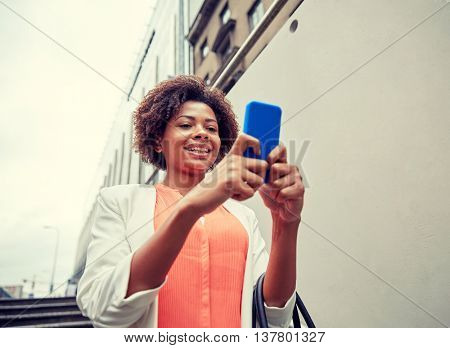 business, technology, communication and people concept - young smiling african american businesswoman with smartphone going down stairs into city underpass